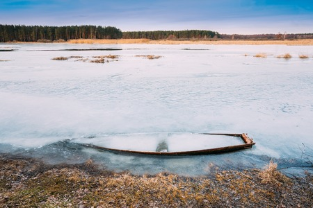 wooden boat: Frozen into ice of river, lake, pond old wooden boat. Abandoned rowing fishing boat in winter river. Forsaken boat at winter river landscape