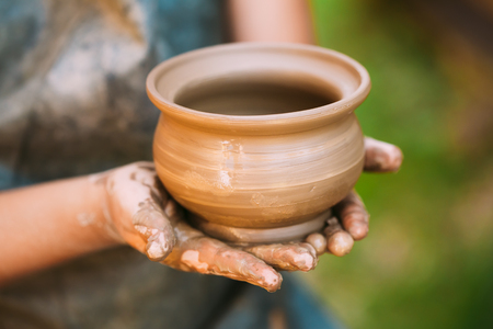 work experience: Handmade of clay pot in female hands. Art and successful work, experience, creativity and inspiration concept. Toned Photo. Stock Photo