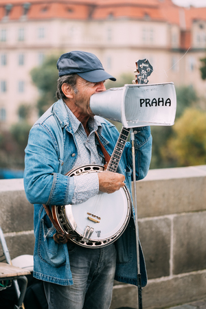busker: PRAGUE, CZECH REPUBLIC - OCTOBER 10, 2014: Street Busker performing jazz songs at the Charles Bridge in Prague. Busking is legal form of earning money on Prague Streets. Editorial