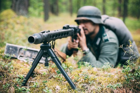 wehrmacht: Hidden unidentified re-enactor dressed as german wehrmacht soldier aiming a machine gun at enemy from trench in forest
