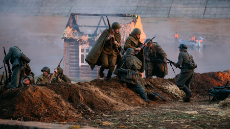 MOGILEV, BELARUS - MAY 08, 2015: Reconstruction of battle for liberation of Mogilev. Reenactors dressed in uniform of World War II Soviet and German soldiers are fighting hand to hand over trenches.