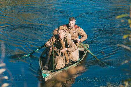 reenaction: Teryuha, Belarus - October 3, 2015: Two unidentified re-enactors dressed as World War II Soviet russian soldier make crossing of river on a wooden boat Editorial