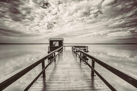 Old wooden pier for fishing, small house shed and beautiful lake or river in background. Black and White Colors.