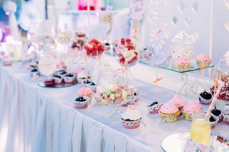 Dessert Sweet Tasty Cupcakes In Candy Bar On Table. Delicious Sweet Buffet. Bright Wedding Decorations Stock Photo