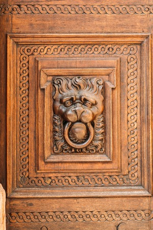 heads old building facade: Lion head wood carving on old wooden door. Decorate detail. Old town Hall in Prague Stock Photo