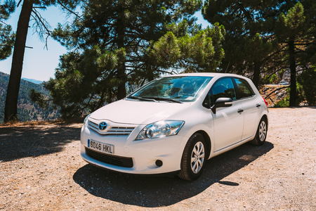 derived: MIJAS, SPAIN - JUNE 19, 2015: White color Toyota Auris car on Spain nature landscape. The Toyota Auris is a compact hatchback derived from the Toyota Corolla