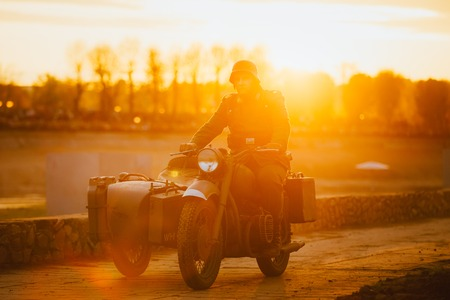 wehrmacht: Unidentified re-enactor dressed as World War II german wehrmacht soldier rides on motorcycle in  rays of sunset sun. Stock Photo