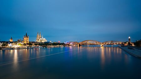 Night View Of St. Martin Church And Cologne Cathedral And Hohenzollern Bridge, Germany. Europe. - a Roman Catholic Gothic Cathedral. Panorama Panoramic View Night Cityscape Stock Photo