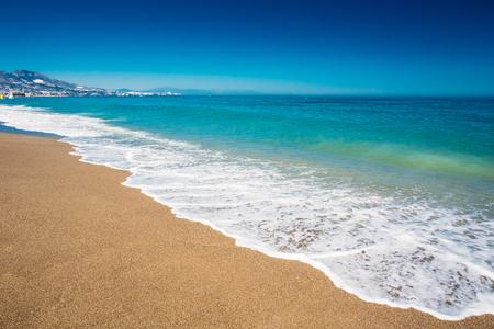 Suaves olas del océano del mar de lavado más de Fondo de la arena de oro. Onda suave del mar Mediterráneo en España
