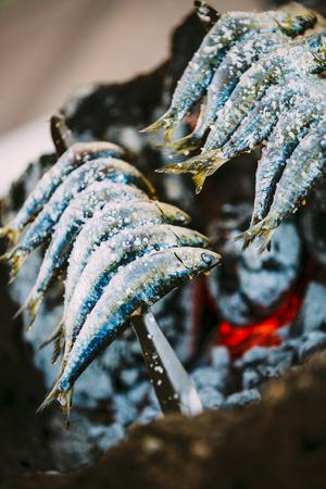 coal fish: Fish Espetos Preparation. Espetos - Skewer With Sardines In Open Fire. National Spanish Cuisine. Stock Photo