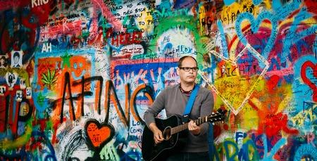 letras musicales: Praga, República Checa - 10 de octubre 2014: El hombre canta canciones de los Beatles, cerca de Muro de John Lennon. Muro está lleno de John Lennon de graffiti inspirado y letras de canciones de los Beatles