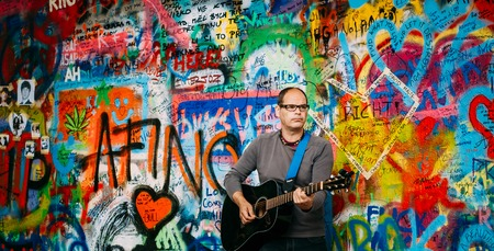 letras musicales: Prague, Czech Republic - October 10, 2014: Man sings Beatles songs near John Lennon Wall. Wall is filled with John Lennon inspired graffiti and lyrics from Beatles songs