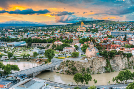 of the holy trinity: Evening View Of Tbilisi At Colorful Sunset, Georgia. Summer Cityscape. On Photograph Visible A New Concert Hall, Avlabar Residence - Presidential Administration Of Georgia, Holy Trinity Cathedral Of Tbilisi, Metekhi Church Stock Photo