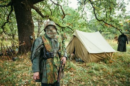 wehrmacht: Hidden unidentified re-enactor dressed as World War II german wehrmacht sniper soldier in forest.