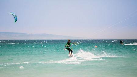 kite surfing: Tarifa, Spain - June 21, 2015: Kite surfing in Tarifa, Spain. Tarifa is most popular places in Spain for kitesurfing. Woman Kite surfer. Editorial