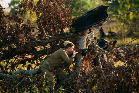 fallen tree: Teryuha, Belarus - October 3, 2015: Unidentified re-enactor dressed as Soviet russian soldier hiding behind a fallen tree and aiming a machine gun at the enemy Editorial