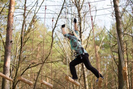 clambering: Gomel, Belarus - April 10, 2015: Young woman in park clambering with ropes in forest. Editorial