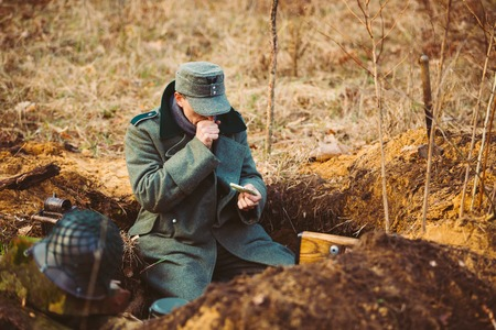 wehrmacht: Pribor, Belarus - April, 04, 2015: Unidentified Re-enactor Dressed As World War German Wehrmacht Soldier In A Trench Settling For Night