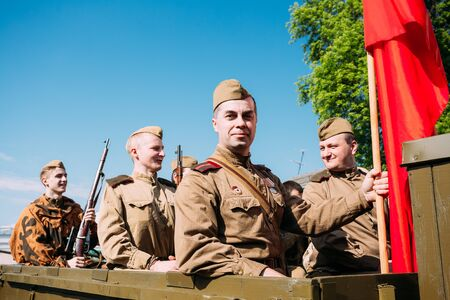 soviet flag: Gomel, Belarus  - May 9, 2016: Group Of Men Sitting In Russian Soviet Military Truck ZIS-5V In Soldiers Uniform With Weapon Of WW2 Time And Victory Red Flag. Preparing For The 9th May Victory Parade
