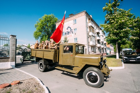 soviet flag: Gomel, Belarus  - May 9, 2016: Russian Soviet Military Truck ZIS-5V With Men On Board Dressed In Soldiers Uniform With Weapon Of WW2 Time, Victory Red Flag. Preparing For The 9th May Victory Parade.