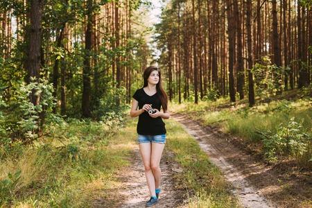 Gelukkig Roodharige Kaukasisch Meisje Jonge Vrouw Fotograaf Lopen en foto's The Old Retro Vintage Camera van de Film In De Zomer Groene Woud. Meisje gekleed in een zwart T-shirt.