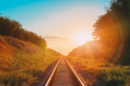 The Scenic Landscape With Railway Going Straight Ahead Through Summer Hilly Meadow To Sunset Or Sunrise In Sunlight. Lense Flare Effect. Stockfoto