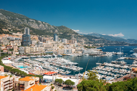 Monaco, Monte Carlo Cityscape. Real Estate Architecture On Mountain Hill Background. Many High-rise Buildings In Downtown Area. Yachts Moored At Town Quay In Sunny Summer Day Stock Photo