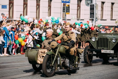 sidecar: Gomel, Belarus - May 9, 2016: The Moving Tricycle Sidecar With Two Men In Soldiers Uniform And Machine Gun Of WW2 Time On Board. A Part Of Demo Parade Procession On Victory Day 9 May. Editorial