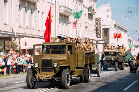 ww2: Gomel, Belarus - May 9, 2016: The Parade Of Russian Soviet Military Cars Of WW2 Time With Re-Enactors Dressed As Soldiers. The Truck ZIS-5V With Red Flag Foreground. Celebrating Victory Day Holiday Editorial