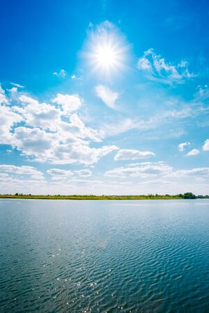riverine: Scenic Riverine Landscape Of Skyline, River Lake Water Surface, Bright Blue Sky With White Clouds, Sun At Zenith. Copyspace Background.