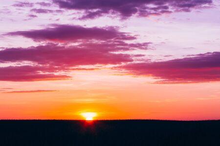 Coucher de soleil, Sunrise Over rural champ de blé. Ciel menaçant lumineuses et sombres au sol. Campagne Paysage Sous Scenic Summer Ciel menaçant Dans Sunset Aube Sunrise. Skyline.