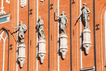 town hall square: Sculptures On The Facade Of The House Of Blackheads In Riga, Latvia. Famous Landmark. Travel Destination. Town Hall Square. Four Statues Named After Neptune, Agreement, Peace, Mercury. Stock Photo