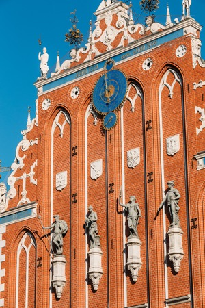 town hall square: Sculptures On The Facade Of  The House Of Blackheads In Riga, Latvia. Famous Landmark. Travel Destination. Town Hall Square. Four Statues Named After Neptune, Agreement, Peace, Mercury. Astronomical Clock and emblems Stock Photo