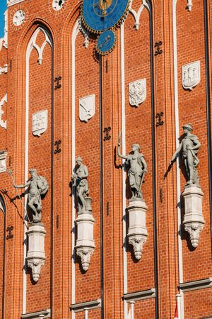 Sculptures On The Facade Of The House Of Blackheads In Riga, Latvia. Famous Landmark. Travel Destination. Town Hall Square. Four Statues Named After Neptune, Agreement, Peace, Mercury. Stock Photo