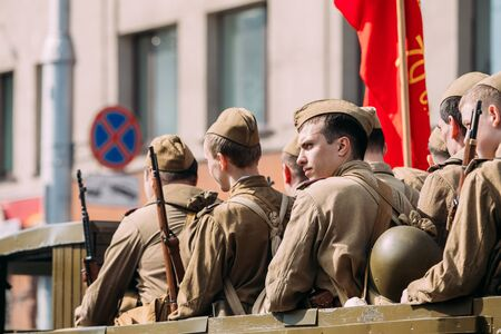soviet flag: Gomel, Belarus - May 9, 2016: Side View Of Men In Disguise Soviet Soldiers With Guns Sitting In Military Truck ZIS-5V Of WW2 Time With Red Flag. Participants Of Parade Celebrating The Victory Day.