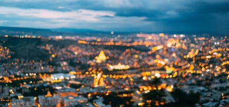 Panoramic Absract Blurred Bokeh Architectural Urban Backdrop Of Tbilisi, Georgia. Real Blurred Colorful Bokeh Background With Defocused Glowing Lights