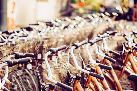 parked bikes: Row Of City Parked Bicycles Bikes For Rent On Sidewalk. Bike Bicycle Parking In European City. Close Up Of Handlebar. Toned Instant Filtered Photo Stock Photo