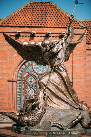 minsk: Minsk, Belarus - May 20, 2015: Statue Of Archangel Michael With Outstretched Wings, Thrusting Spear Into Dragon near Red Catholic Church Of St. Simon And St. Helena On Independence Square In Minsk, Belarus