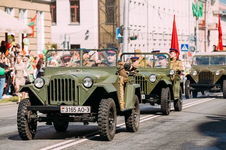 ww2: Gomel, Belarus - May 9, 2016: The Moving Column Parade Of Russian Soviet Military Cars Trucks Of WW2 Time With People In Soldiers Uniform On Boards With Red Flags. Celebrating The Victory Day Holiday
