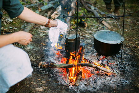 marching: Food Is Cooked Over A Fire In An Old Marching Pot. Stock Photo