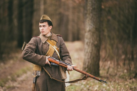 reenaction: Pribor, Belarus - April 04, 2015: Young unidentified re-enactor dressed as Soviet soldier gunner goes along a forest road.