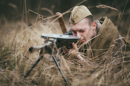 Pribor, Belarus - April 04, 2015: Unidentified re-enactor dressed as Soviet russian soldier aiming a machine gun at enemy