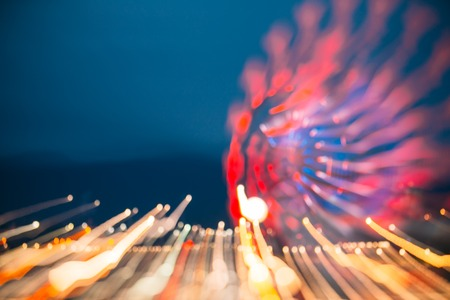 Abstract Motion Blur Image Of Brightly Red Illuminated Ferris Wheel In Amusement City Park On Blue Evening Sky, Bokeh Boke Background.