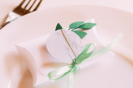 Wedding Candy-box Lies On A Plate. Bomboniere Also Known As Favors, Are Gifts Given By Hosts To Their Guests On Special Occasions Such As Bar And Bat Mitzvahs, Weddings Etc. Decoration For Wedding Celebration.