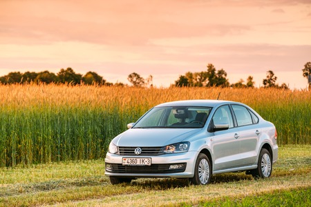 Gomel, Belarus - June 6, 2016: Volkswagen Polo Car Parking On Wheat Field. Sunset Sunrise Dramatic Sky On A Background In Sunny Evening.