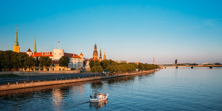 Scenic View To Promenad Of Daugava, In Riga, Latvia. Old Church Towers And Medieval Castle On Background. Seafront Named Ab Dambis. Evening  View With Blue Sky. Travel Destination. Urban View Stock Photo