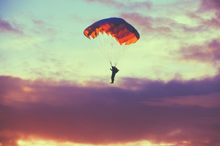 Skydiver On Colorful Parachute In Sunny Clear Sky. Active Hobbies. Purple Colors Sunset Or Sunrise Sky. Stock Photo