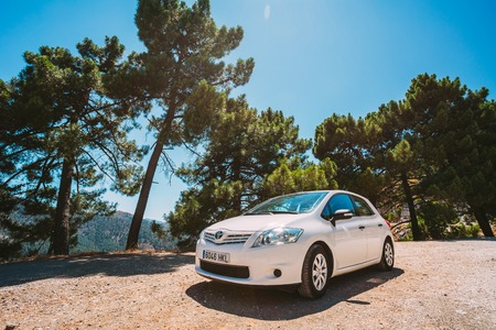 Mijas, Spain - June 19, 2015: White color Toyota Auris car on Spain nature landscape. The Toyota Auris is a compact hatchback derived from the Toyota Corolla Editorial