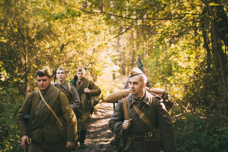 reenaction: Teryuha, Belarus - October 3, 2015: Group of unidentified re-enactors dressed as Soviet russian soldiers goes along forest road. Editorial