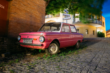 Tbilisi, Georgia - May 19, 2016: The Parked Rarity Tuning Pink Minicar ZAZ-968M Zaporozhets On The Street Paved By The Cobblestone In Old District Of The City In Summer Evening.